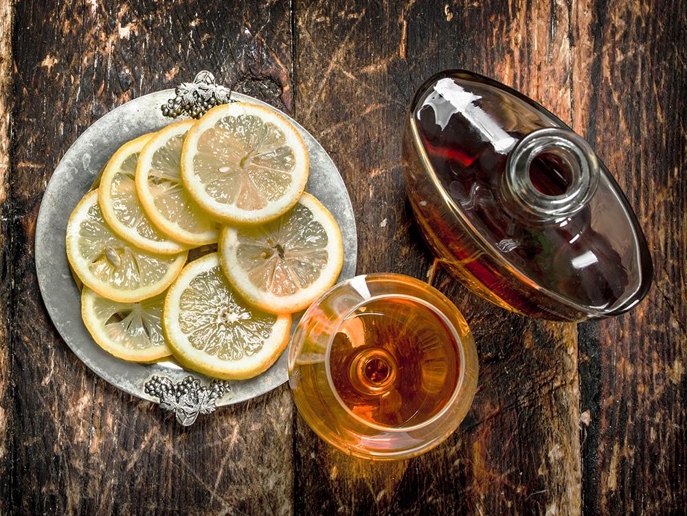 Коньяк с нарезанным лимоном на тарелке