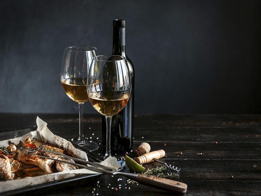 Приготовленная рыба, бокалы и бутылка вина