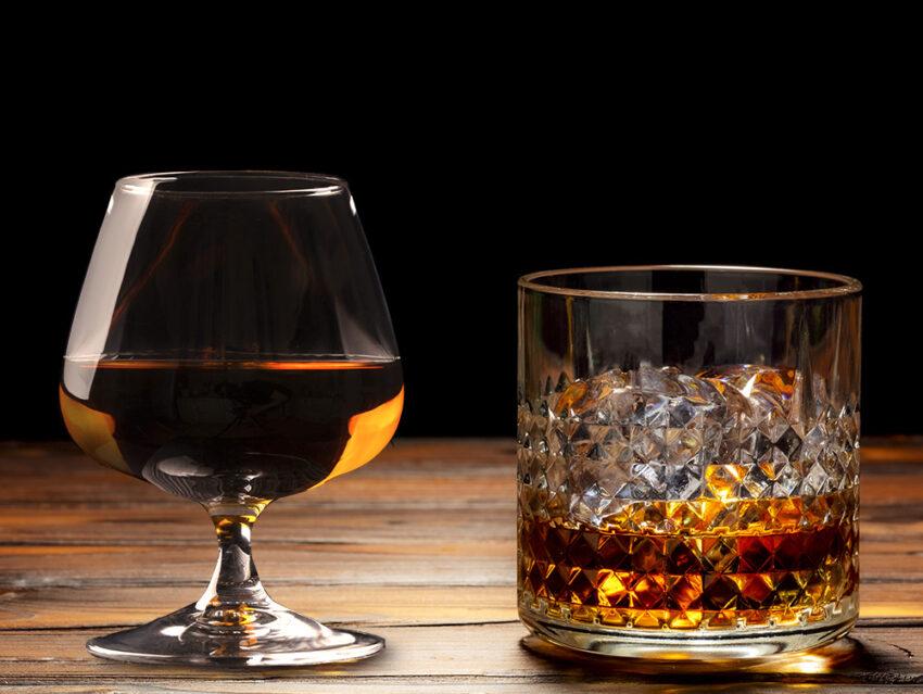 Бокал коньяка и бокал виски со льдом