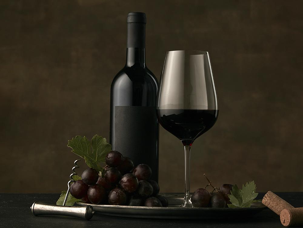 Бокал и открытая бутылка вина