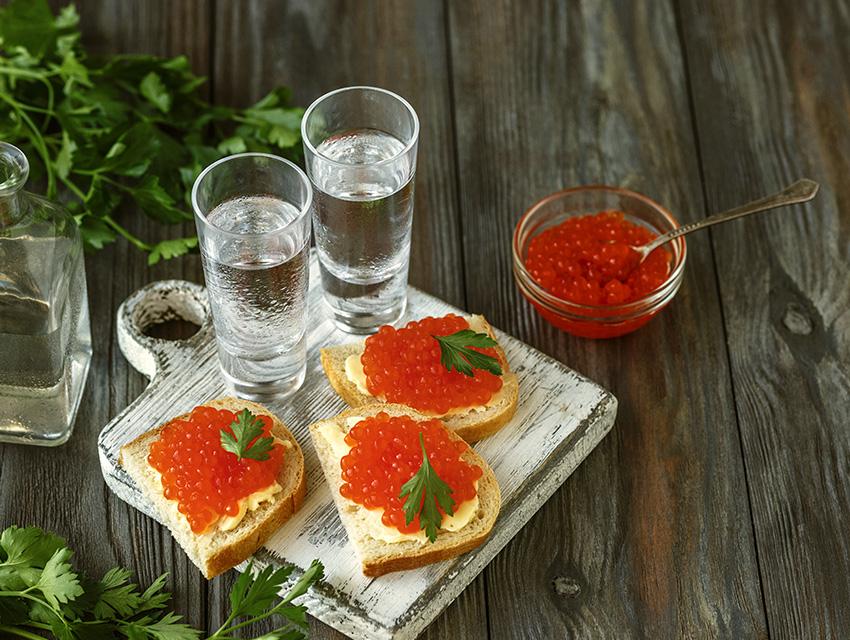 Водка в рюмках с бутербродами с красной икрой